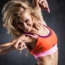 Young woman jumps while making aerobics exercises on gray background